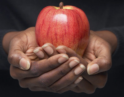 A picture of an red apple in someones hands